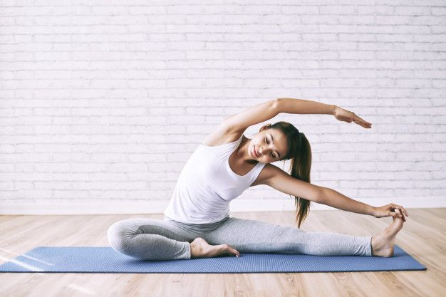 young-woman-stretching-floor-as-morning-drill-develop-flexibility_1098-20278
